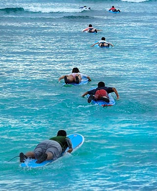 After surfing lesson, surfers head out to surf