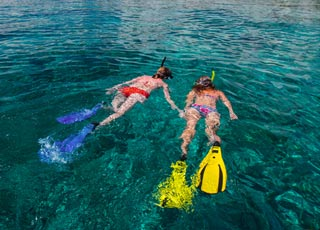 two girls snorkeling over coral reef