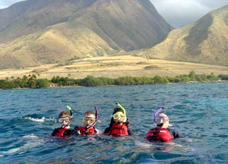 snorkeling in west maui with the west maui mountains in background